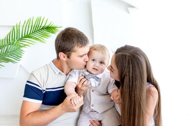 Jonge moeder en vader zoenen een kind, ouders met hun zoon, familiedag, gelukkig gezin