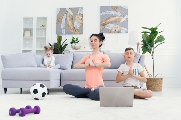 Jonge moeder en zoon beoefenen yoga met laptop op de vloer thuis.