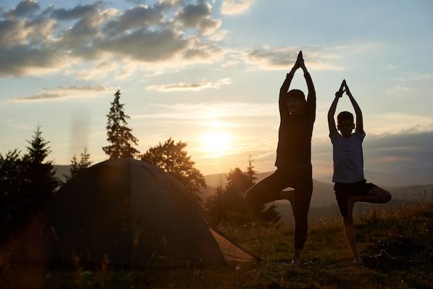 Jonge moeder en zoon die gymnastiek doen bij de bergen bij zonsondergang. moeder en zoon doen yoga. vrouw en kind opleiding in de natuur. buitensport. gezonde sportlevensstijl.