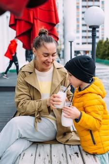 Jonge moeder en zoon hebben plezier en drinken buiten milkshake
