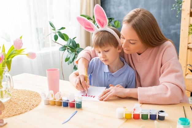 Jonge moeder en zoon in konijnenoren die aan tafel zitten en paaskaart met gouache maken