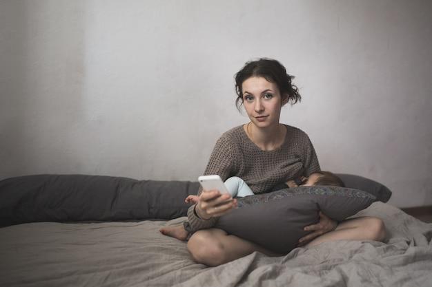 Jonge moeder geeft baby en smartphone, levensstijl,