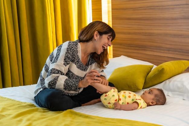 Jonge moeder geniet met haar baby in het bed van haar slaapkamer, jonge blanke eerste keer met haar vier maanden oude baby