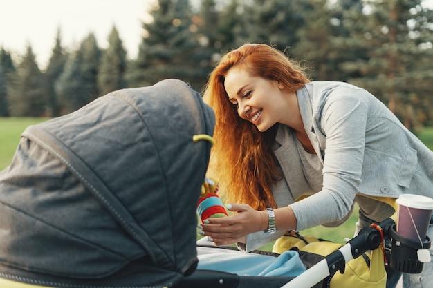 Jonge moeder genieten van wandeling in park met baby