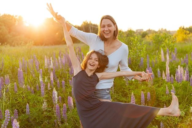Jonge moeder haar kind buiten omarmen op zomer veld met bloeiende wilde bloemen