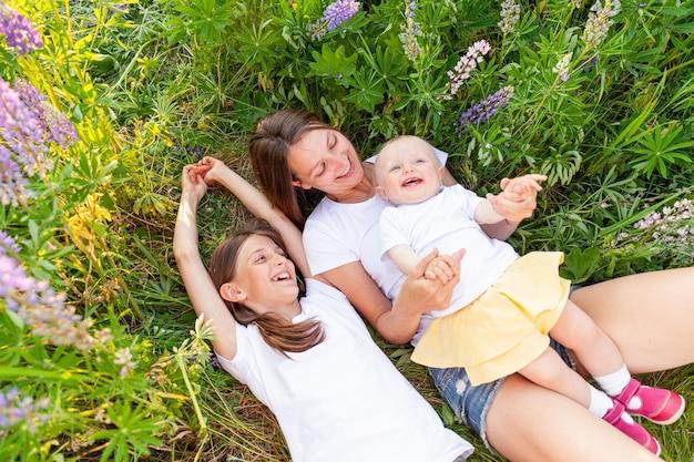 Jonge moeder haar kinderen buiten omarmen, liggend op zomer veld met bloeiende wilde bloemen