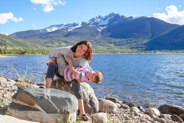 Jonge moeder haar zoon knuffelen in de buurt van het meer met een prachtig uitzicht op de bergen op de achtergrond.