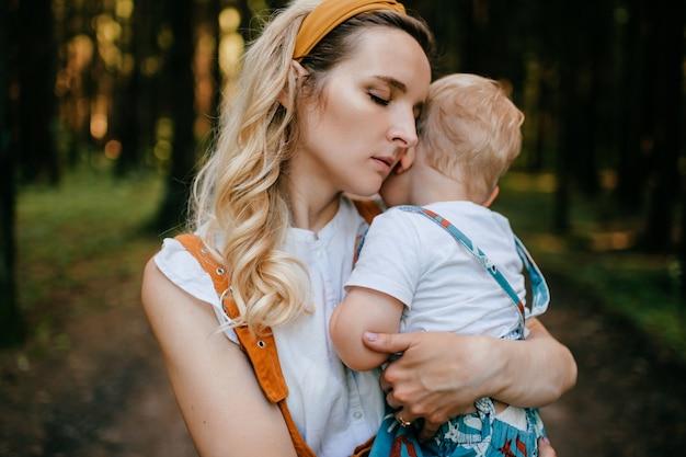 Jonge moeder haar zoon knuffelen in het bos