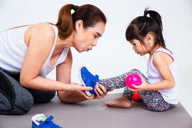 Jonge moeder helpen schattige dochter schoenen dragen