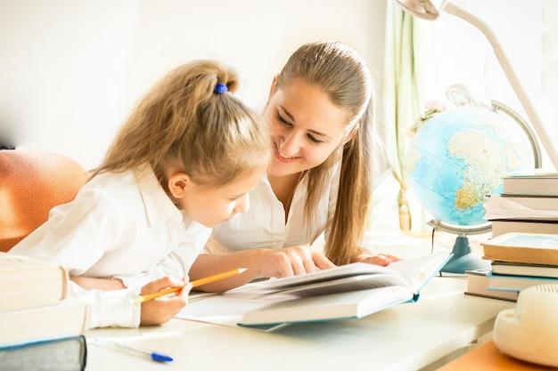 Jonge moeder helpt dochter met huiswerk