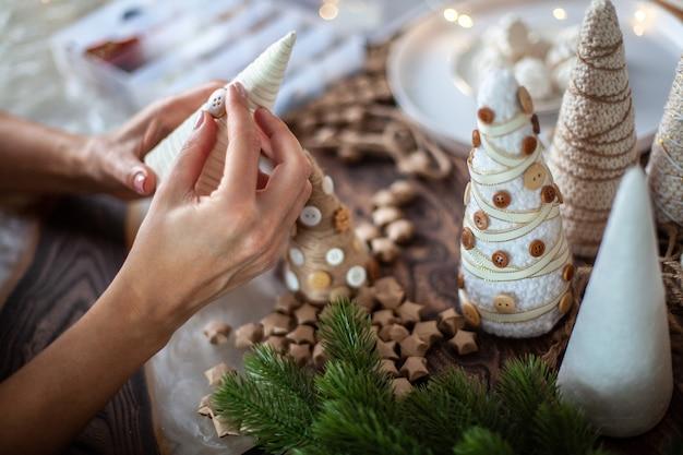 Jonge moeder helpt dochter voor het inpakken van schuimkegel met touw of garen en het maken van verschillende maten kerstbomen voor tafeldecoratie. concept van voorbereiding voor feestelijk seizoen en feest.