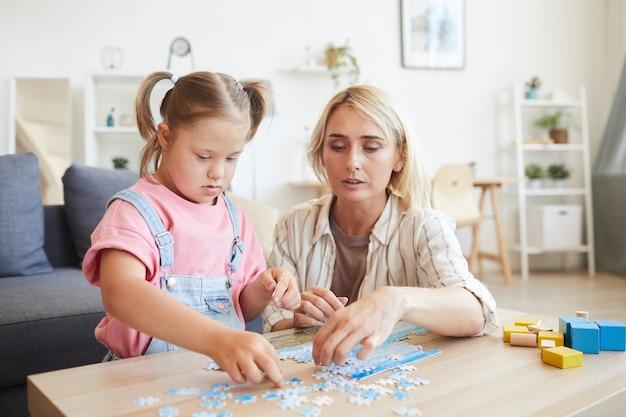 Jonge moeder helpt haar dochter met het syndroom van down puzzels verzamelen aan de tafel in de kamer