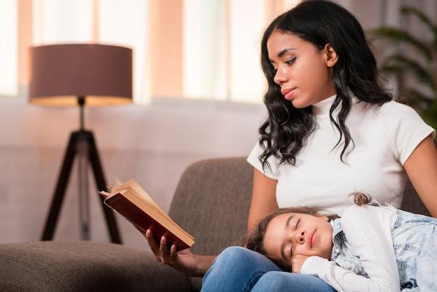 Jonge moeder het lezen van verhalen voor dochter