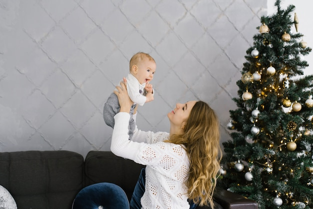 Jonge moeder hief haar zoon in haar armen en glimlacht naar hem. ze vieren kerstmis en nieuwjaar in de woonkamer met een kerstboom