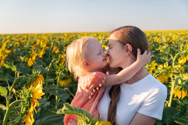 Jonge moeder houdt dochtertje op veld met zonnebloemen achtergrond