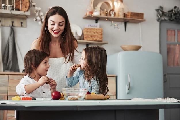 Jonge moeder houdt ervan wanneer haar dochters tevreden zijn. de jonge mooie vrouw geeft de koekjes terwijl zij dichtbij de lijst met speelgoed zitten
