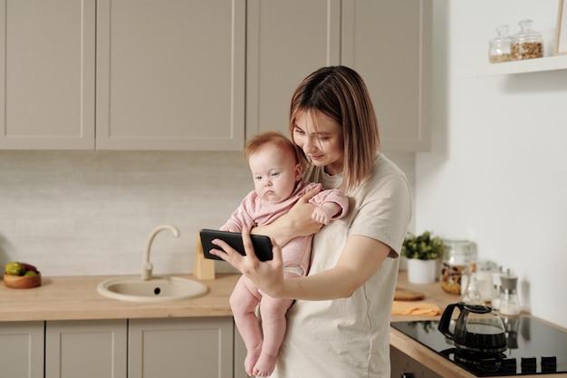 Jonge moeder houdt haar dochtertje en smartphone vast tijdens interactie via videochat