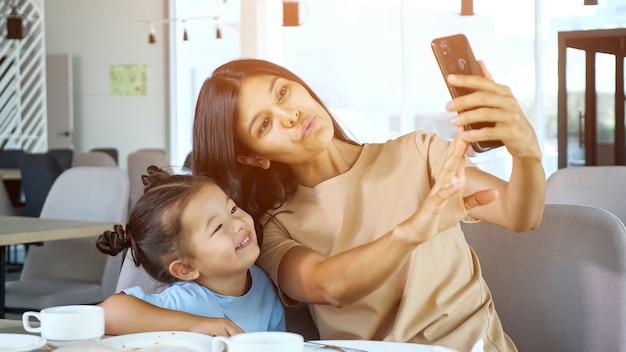 Jonge moeder houdt smartphone vast en maakt selfie met dochter