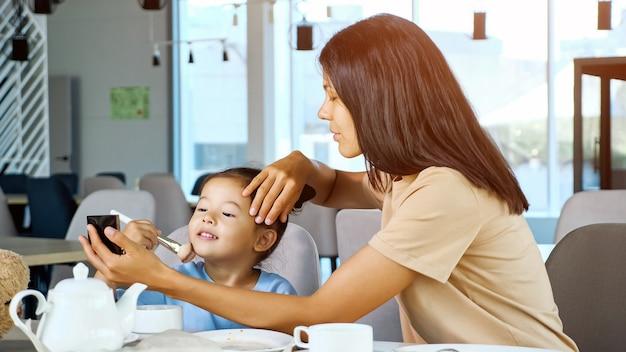 Jonge moeder houdt spiegel vast en meisje beweegt borstel met poeder