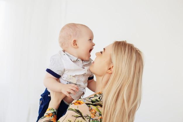 Jonge moeder houdt zoon in haar armen. het concept van kindertijd