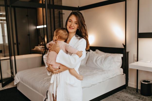 Jonge moeder in badjas die baby in luier houdt en camera met glimlach tegen wit bed bekijkt.