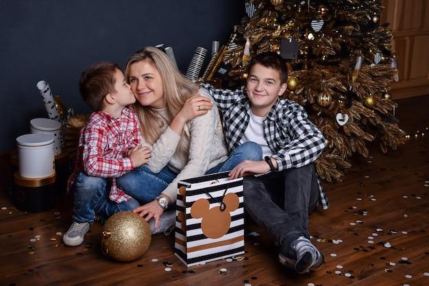 Jonge moeder in de woonkamer van het nieuwe jaar zit op de grond met geschenken en twee zonen en glimlacht