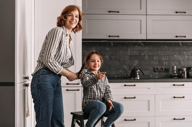 Jonge moeder in overhemd en spijkerbroek staat naast haar dochter zittend op een stoel.