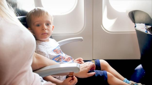 Jonge moeder kalmeert haar zoontje voor de eerste vlucht in het vliegtuig.