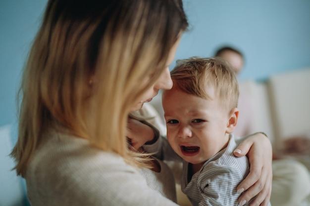 Jonge moeder kalmerende huilende zoon