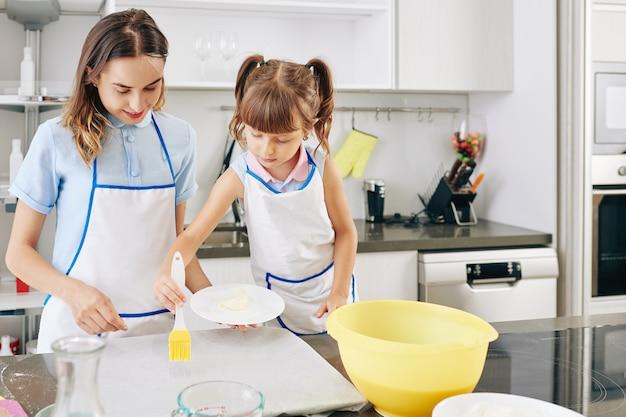 Jonge moeder kijken preteen meisje met siliconen borstel bij het aanbrengen van boter op perkamentpapier