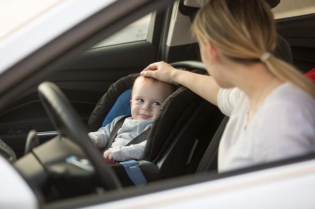 Jonge moeder kijkt naar babyjongen die in de auto in het babyzitje zit
