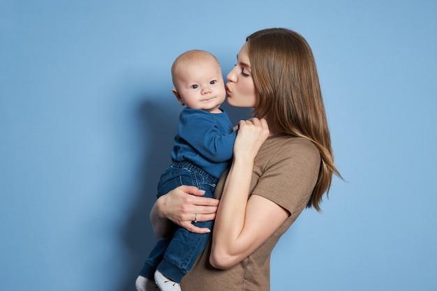 Jonge moeder knuffelt en kust haar zoontje