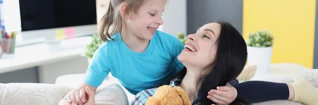 Jonge moeder knuffelt haar dochter na ruzie