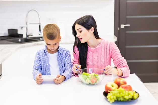 Jonge moeder kokende salade terwijl haar zoon op de telefoonspelen in de keuken speelt