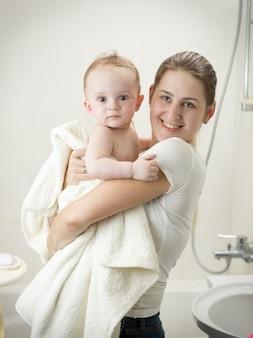 Jonge moeder kust haar baby in de badkamer na het baden
