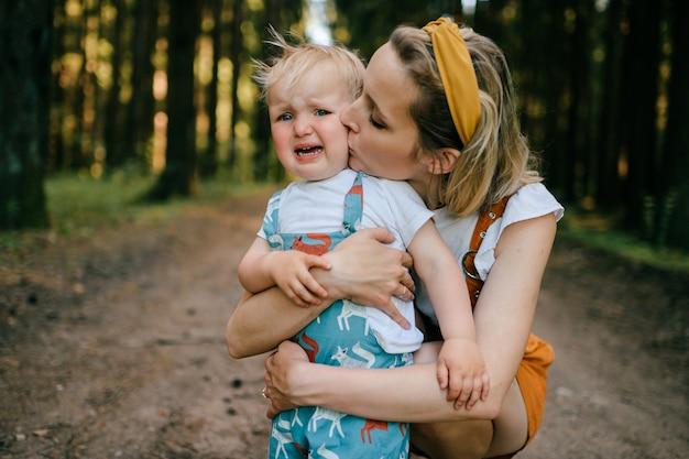 Jonge moeder kuste haar huilende zoon in het bos