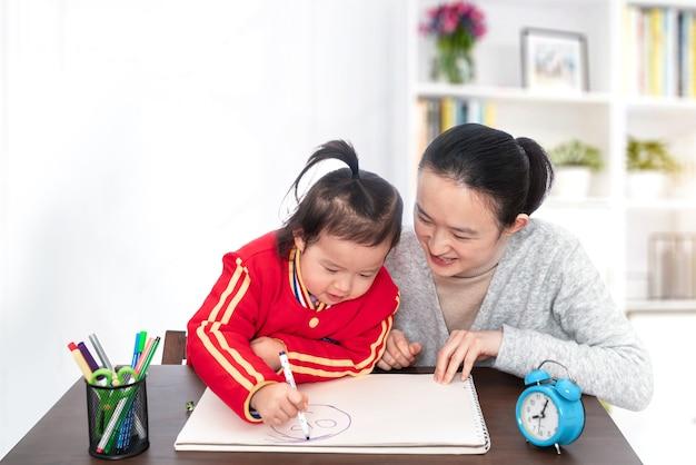 Jonge moeder leert dochter schilderen