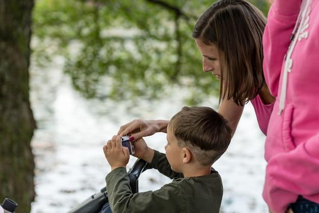 Jonge moeder leert haar jongen buiten in het park foto's te maken met een compactcamera