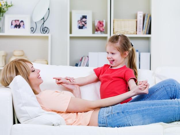 Jonge moeder liggend op de bank en spelen met haar gelukkige liefdevolle dochtertje - binnenshuis
