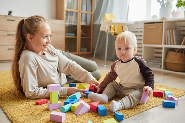 Jonge moeder liggend op de vloer en spelen met haar zoontje in de woonkamer