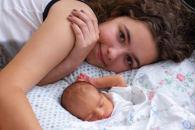 Jonge moeder ligt op bed in de buurt van haar slapende pasgeboren baby