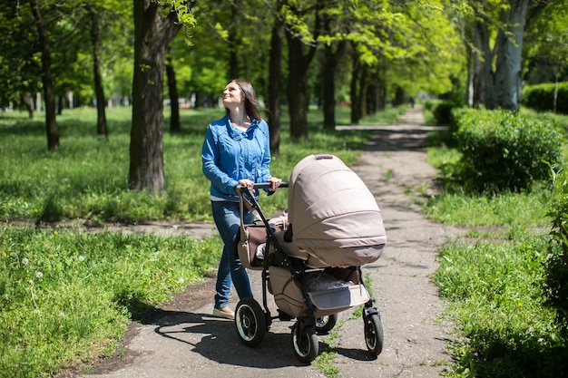 Jonge moeder loopt en duwt een kinderwagen in het park