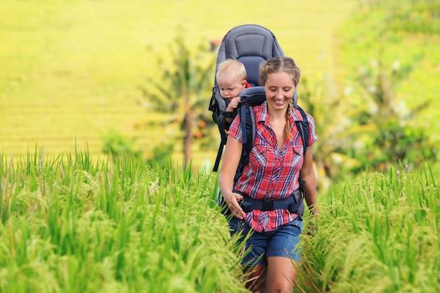 Jonge moeder loopt in tropische rijstvelden, draagt klein kind in draagzak rugzak.