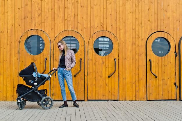 Jonge moeder loopt met een kind in een kinderwagen op de achtergrond van industriële deuren met patrijspoorten.