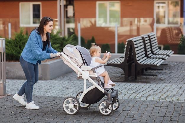 Jonge moeder loopt met haar baby en draagt het in een mooie kinderwagen.