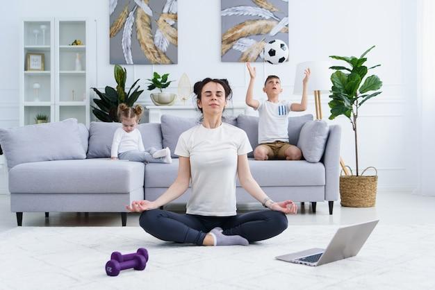 Jonge moeder mediteren in lotus yoga positie terwijl haar kinderen thuis spelen