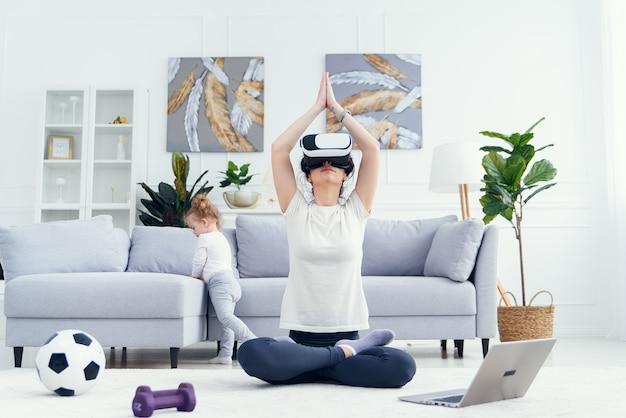 Jonge moeder mediteren in yoga lotuspositie met behulp van een bril terwijl haar dochter tekenfilms bekijkt
