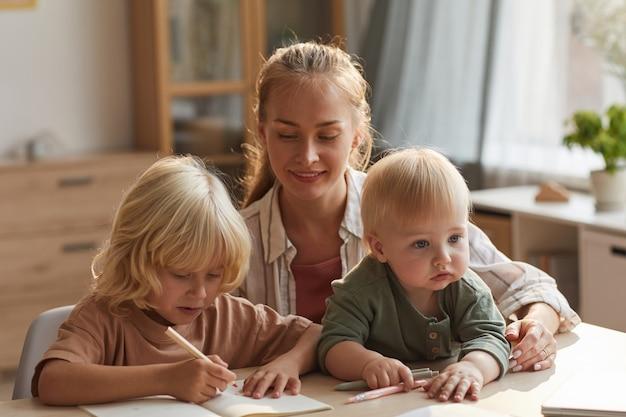 Jonge moeder met baby aan de tafel zitten en haar oudste zoon helpen met huiswerk