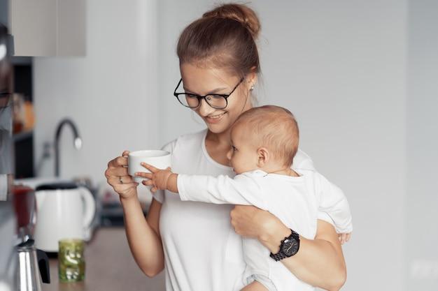 Jonge moeder met baby hebben plezier in de keuken thuis