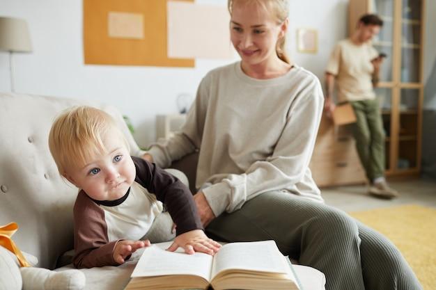 Jonge moeder met baby spelen op de bank en thuis een boek lezen met hun vader